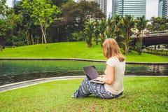 Młoda kobieta w przypadkowej sukni używać laptop w tropikalnym parku na tle drapacze chmur komputerowy filiżanki kawy koncepcję l Zdjęcia Stock