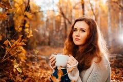 Młoda kobieta w puloweru i cajgu napoju relaksującej herbacie na jesieni tle Fotografia Stock