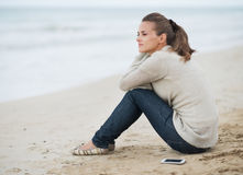 Młoda kobieta w pulowerze z telefonu komórkowego obsiadaniem na osamotnionej plaży obrazy royalty free