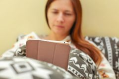 Młoda kobieta w pyjama, kłaść w łóżku, zakrywającym z duvet, workin zdjęcia royalty free