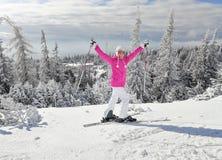 Młoda kobieta w różowej narciarskiej kurtce z nartami na jej ciekach zdjęcia royalty free