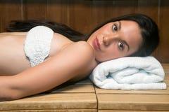 Młoda kobieta w ręcznikowy relaksować na ławce w sauna Obraz Royalty Free
