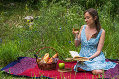 Młoda kobieta w romantycznej błękit sukni przy pinkinem Dziewczyna czyta Zdjęcia Stock