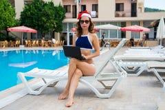 Młoda kobieta w Santa Claus kapeluszowym działaniu na laptopie basenem, boże narodzenia być na wakacjach w tropikalnym kraju Kobi zdjęcia royalty free