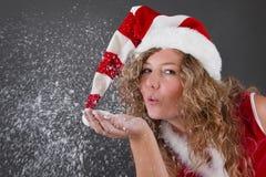 Młoda kobieta w Santa kapeluszowych podmuchowych płatkach śniegu od ona ręka Fotografia Stock