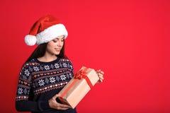 Młoda kobieta w Santa kapeluszu z prezenta pudełkiem na koloru tle świętuje świętowania bożych narodzeń córki kapeluszy macierzys Obraz Stock