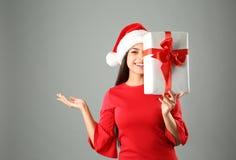 Młoda kobieta w Santa kapeluszu z prezenta pudełkiem na popielatym tle świętuje świętowania bożych narodzeń córki kapeluszy macie Fotografia Stock