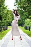 Młoda kobieta w seksownej długiej szarości sukni fotografia stock