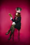 Młoda kobieta w similitude Hatter czytelniczej książki obsiadanie Zdjęcia Stock