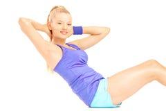 Młoda kobieta w sportswear robi ab ćwiczeniom Zdjęcia Stock
