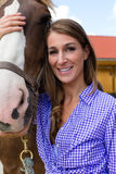Młoda kobieta w stajence z koniem w świetle słonecznym Fotografia Royalty Free