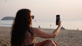 Młoda kobieta w swimsuit i okularach przeciwsłonecznych bierze obrazki złoty zmierzchu morze z telefonu obsiadaniem na plaży Dzie zbiory