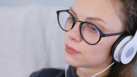Młoda kobieta w szkłach i hełmofonach słucha muzykę, twarz w górę zbiory