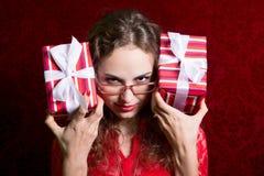 Młoda kobieta w szkłach z dwa paskował prezentów pudełek gapienia w t Zdjęcie Stock