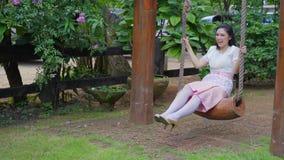 Młoda kobieta w Tajlandzki tradycyjny smokingowy relaksować na drewnianej huśtawce zbiory