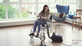 Młoda kobieta w wózku inwalidzkim czyścił z próżniowym cleaner zdjęcie wideo