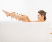 Młoda kobieta w wannie używać ciała muśnięcie na nodze Obrazy Royalty Free
