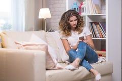 Młoda kobieta w wnętrzu na leżance komunikuje b w domu obraz stock