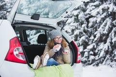 Młoda kobieta w woolen kapeluszu siedzi w bagażniku samochód i pije gorącej herbaty Zdjęcie Royalty Free