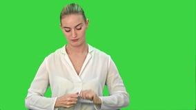 Młoda kobieta w złości rozdziera prześcieradło papier, rzuca je przy kamerą na Zielonym ekranie, Chroma klucz zbiory wideo