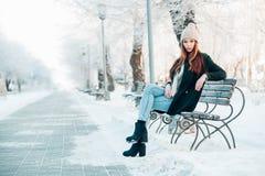 Młoda kobieta w zima parka obsiadaniu na ławce Obrazy Royalty Free