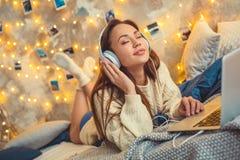 Młoda kobieta weekend w domu dekorował sypialnię słucha ulubiona piosenka obraz stock