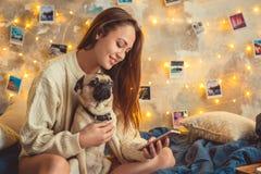 Młoda kobieta weekend w domu dekorował sypialnię z psim używa smartphone obraz royalty free