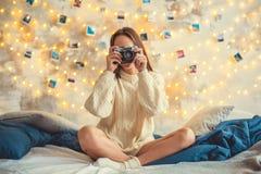 Młoda kobieta weekend w domu dekorował sypialni obsiadanie bierze fotografie fotografia stock