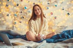 Młoda kobieta weekend w domu dekorował sypialni obsiadanie pije czekoladę obrazy royalty free