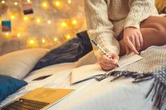 Młoda kobieta weekend w domu dekorował sypialni siedzącego writing w organizatorze zdjęcia stock