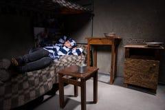 Młoda kobieta więzień jest ubranym więzienie mundur gubił w myśli Zdjęcia Stock