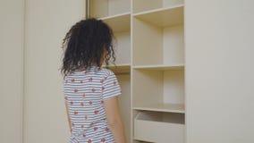 Młoda kobieta wprawiać w zakłopotanie przez jej pustej garderoby zdjęcie wideo