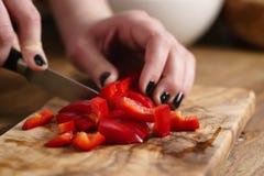 Młoda kobieta wręcza ciapaniu czerwonego dzwonkowego pieprzu na kuchennym stole Zdjęcia Stock