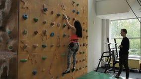 Młoda kobieta wspina się na pięcie ścianie pod nadzorem instruktor indoors zdjęcie wideo