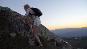 Młoda kobieta wspina się wysoką skałę przy zmierzchem lub przy świtem zbiory