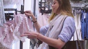 Młoda kobieta wybiera bieliznę w sklepie odzieżowym zbiory