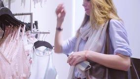 Młoda kobieta wybiera bieliznę w sklepie odzieżowym zdjęcie wideo