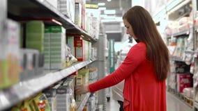 Młoda kobieta wybiera dziecka jedzenie w supermarkecie, matka wybiera jedzenie dla ich dziecka w rynku, dziewczyna stojaki blisko zbiory wideo