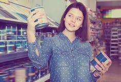 Młoda kobieta wybiera nową ścienną farbę Zdjęcia Royalty Free