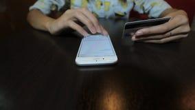 Młoda kobieta wybiera numer liczbę kredyt lub karta debetowa który trzyma w lewej ręce zbiory