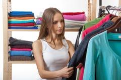 Młoda kobieta wybiera odzieżowego zdjęcie stock