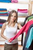 Młoda kobieta wybiera odzieżowego zdjęcia stock