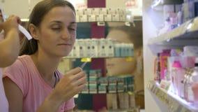 Młoda kobieta wybiera pachnidło przy piękno działem supermarket z ldaughter zdjęcie wideo