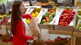 Młoda kobieta wybiera paprykę na półkach sklepowych zdjęcie wideo