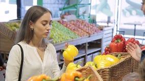 Młoda kobieta wybiera słodkiego pieprzu pozycję w sklepie indoors Lokalizować przy kontuarem z koszami warzywa zbiory wideo