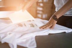Młoda kobieta wyciągał papier od wodoodpornego filmu na tkaninie przy sho fotografia stock