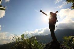 Młoda kobieta wycieczkowicza otwarte ręki przy wschodu słońca halnym szczytem Zdjęcia Stock