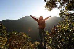 Młoda kobieta wycieczkowicza otwarte ręki wschód słońca na halnym szczycie Zdjęcie Stock