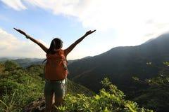Młoda kobieta wycieczkowicza otwarte ręki wschód słońca na halnym szczycie Obrazy Stock