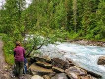 Młoda kobieta wycieczkowicza utworzenie jej campsite przy dalekim obozowiskiem wzdłuż pięknej rzeki otaczał zielonym wiecznozielo obrazy stock